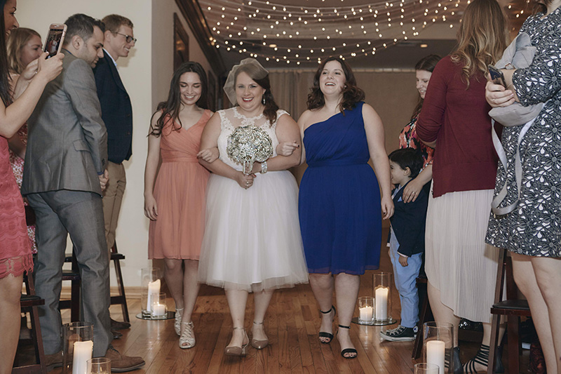 bride walking down the isle with sisters