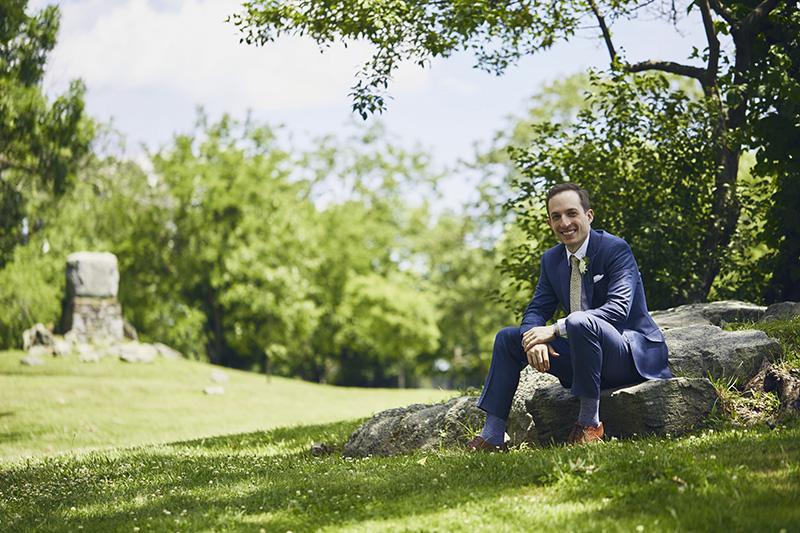 groom sitting on a rock