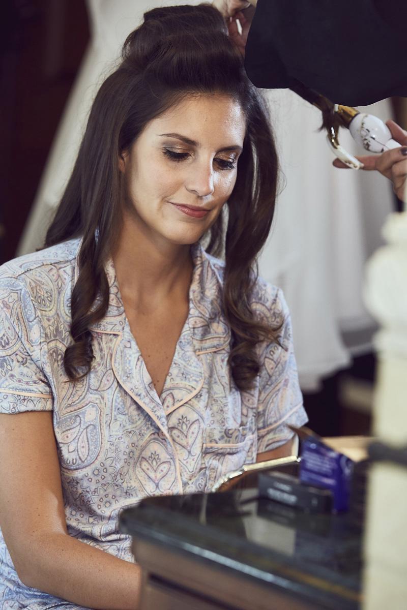 Bride getting hair done by hair stylist