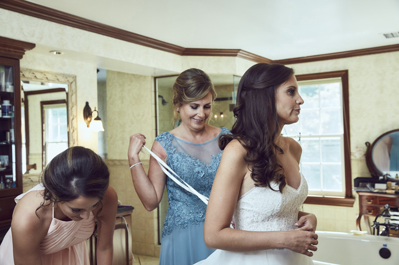 bride's mother helping bride  to put the wedding dress on