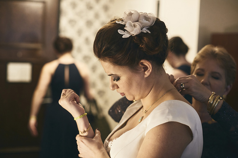 bride putting the wedding jewelry