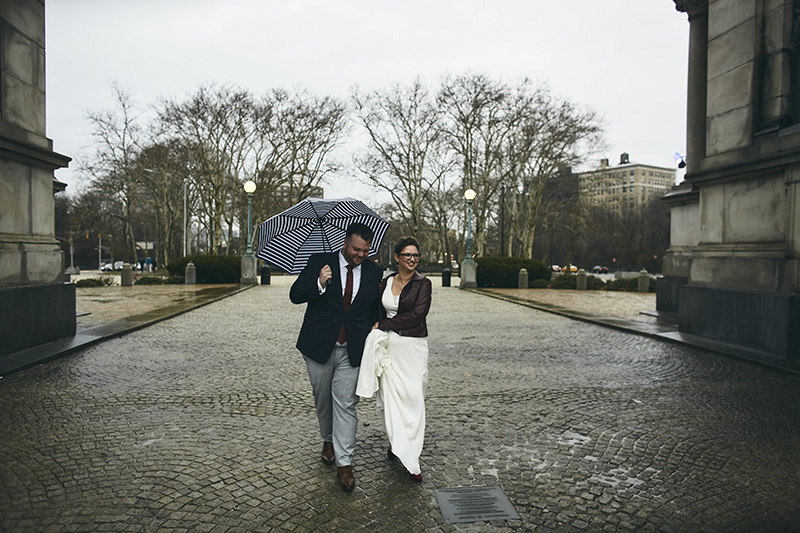 Bride and groom walking on  the rainy day  in NYC