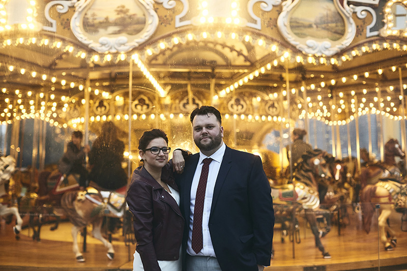 Bride and groom posing by the NYC carousel