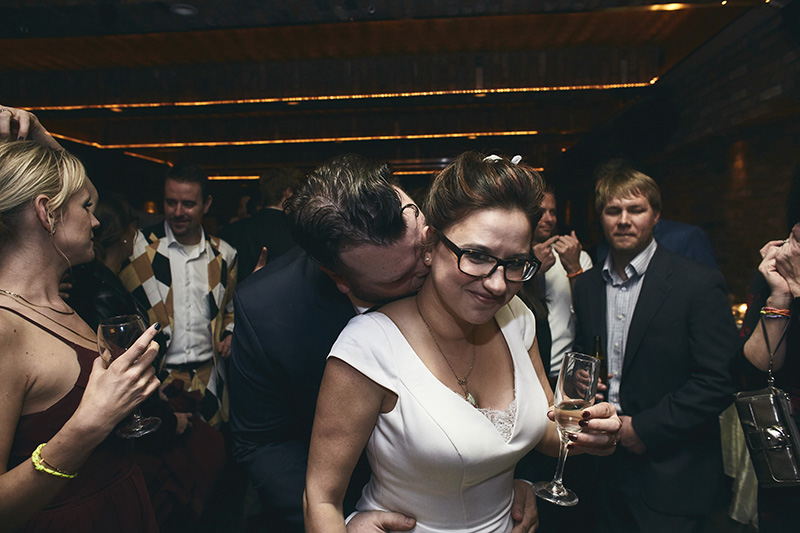 Groom kissing bride on the neck