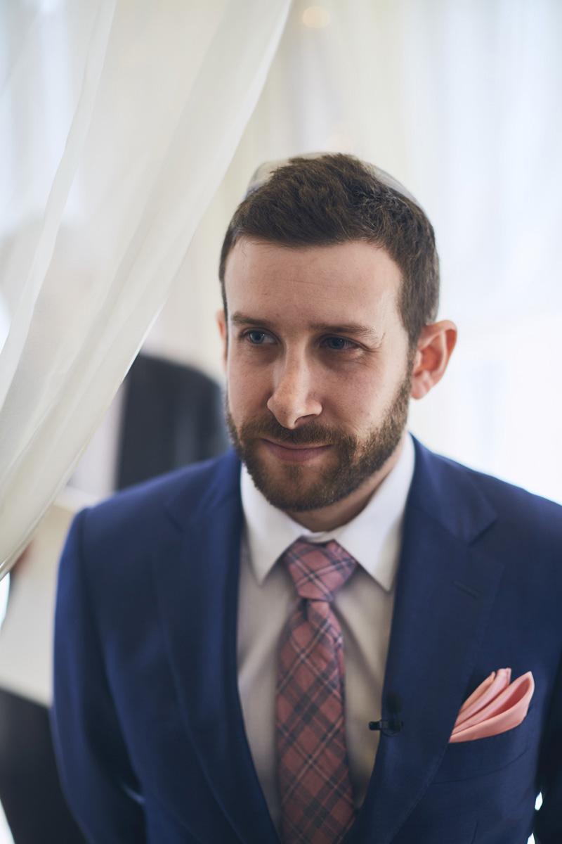 groom looking at bride walking down the aisle