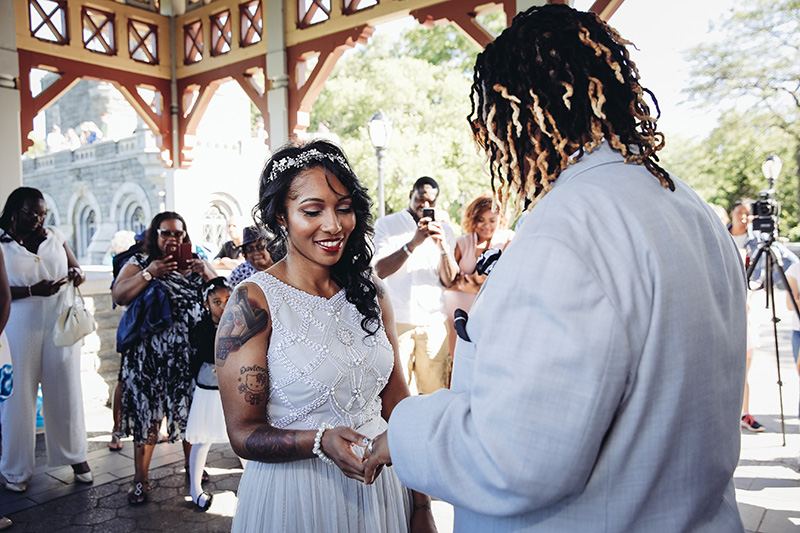 Bride putting ring on bride