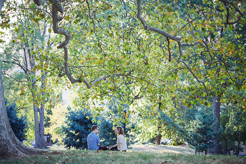 young couple sitting under the tree