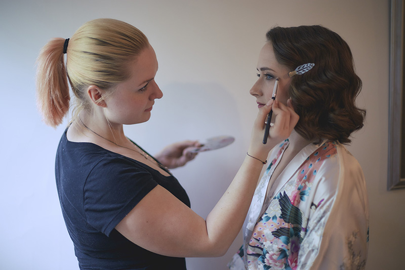 bride putting the make up on