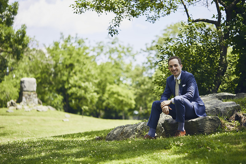 groom sitting on a rock