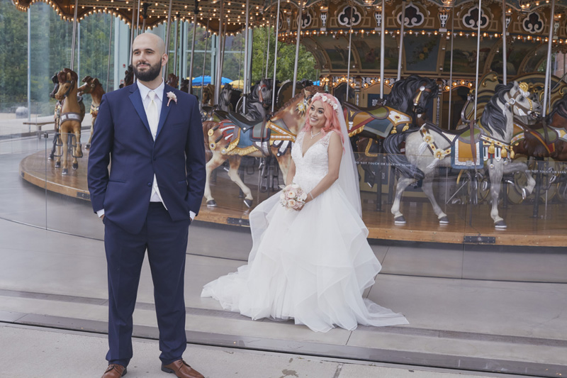 bride and groom in front of the carussell