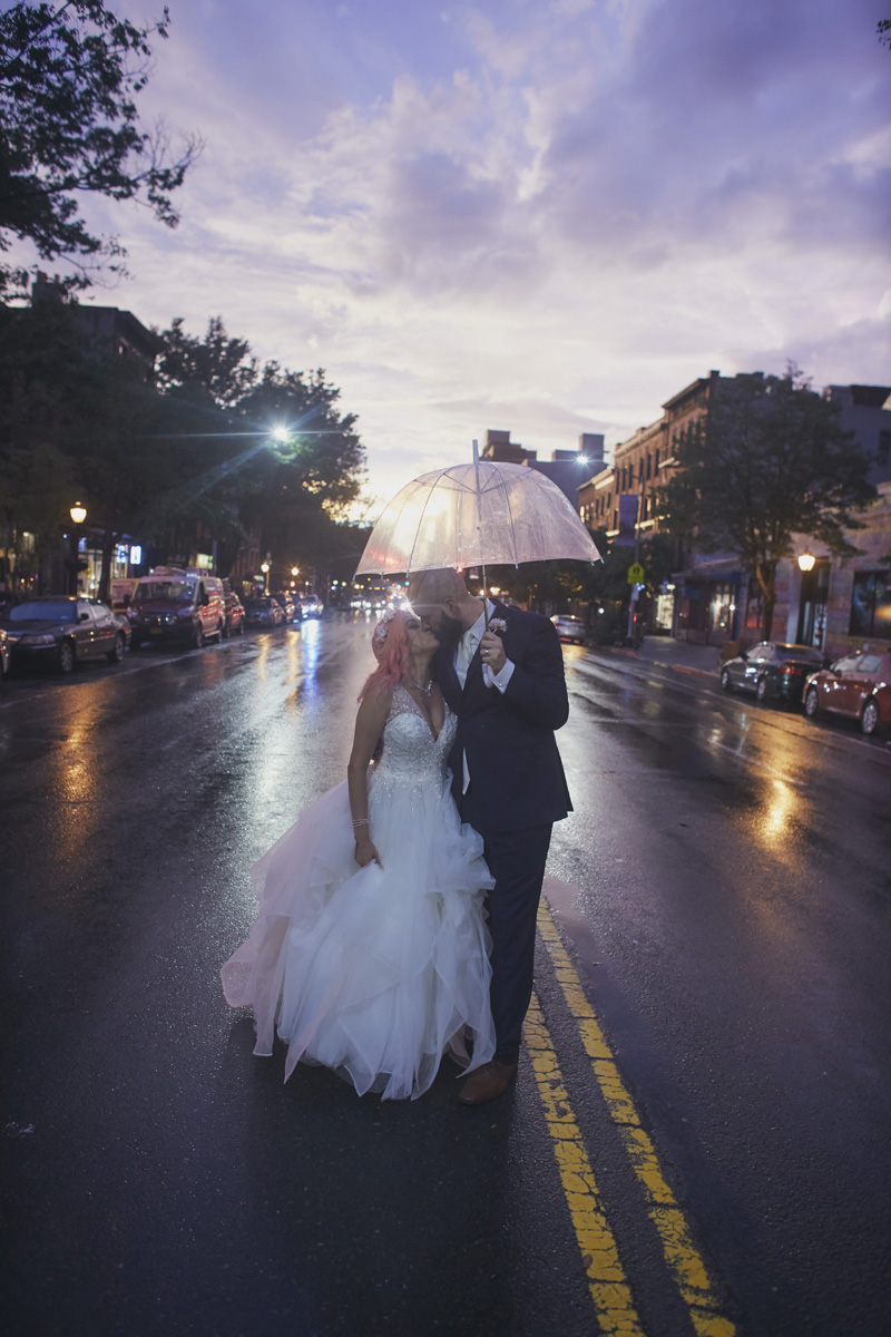 bride and groom kissing on the rain