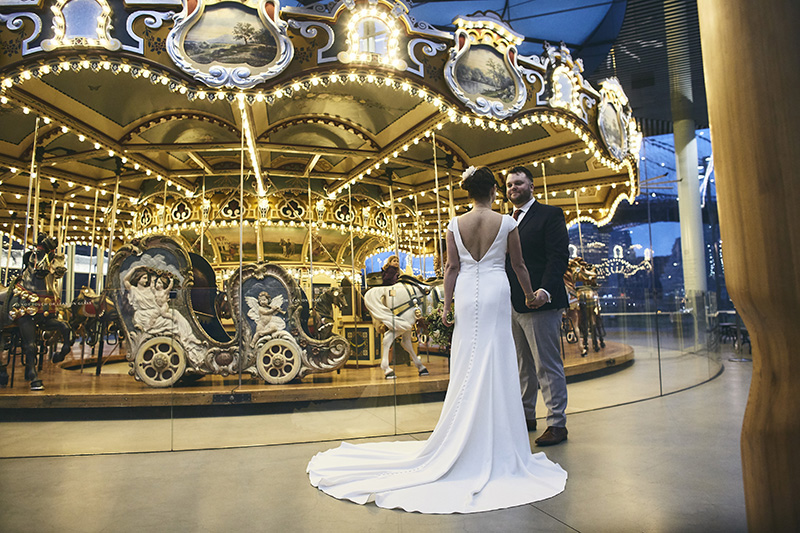Bride and groom posing by the carousel in NYC
