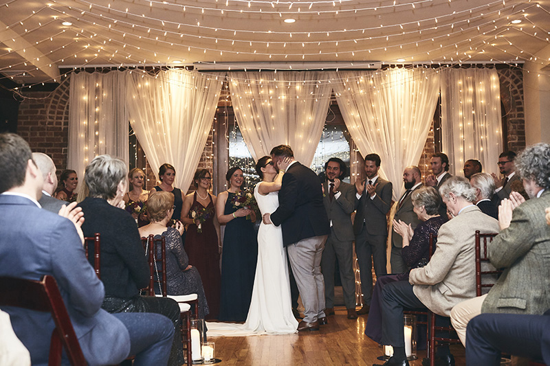 Bride and groom kissing in the wedding room