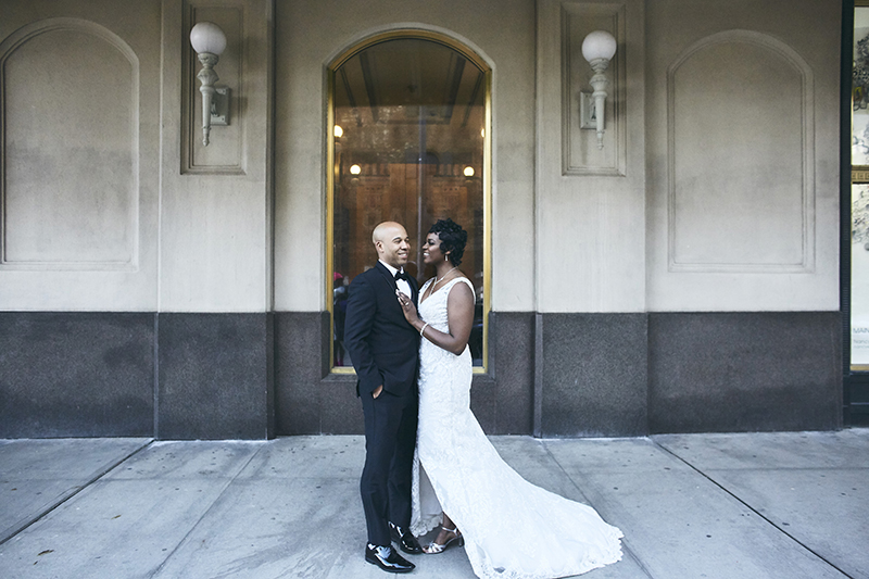 Bride and groom posing in front of the shopwindow