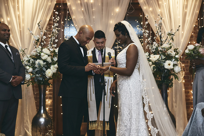 Groom putting the ring on brides finger