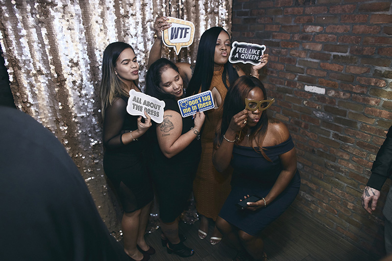 Guests posing at the wedding with photo booth props