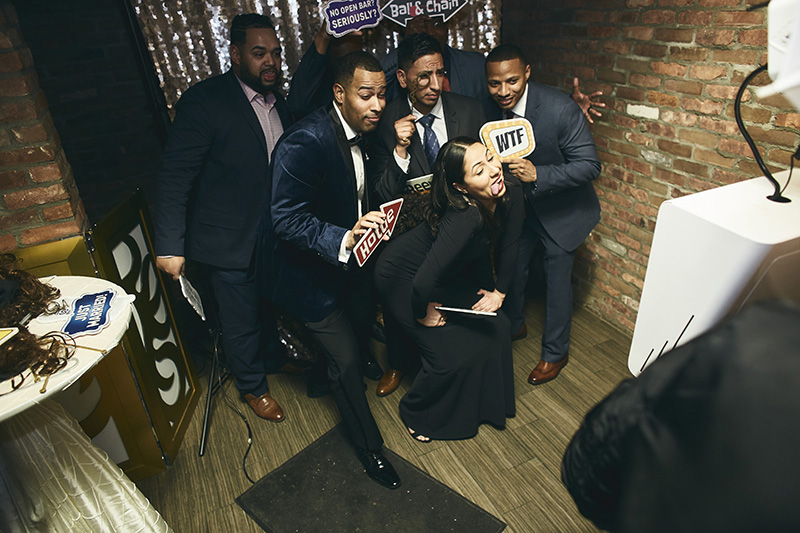 Guests posing at the wedding  party with photo booth props
