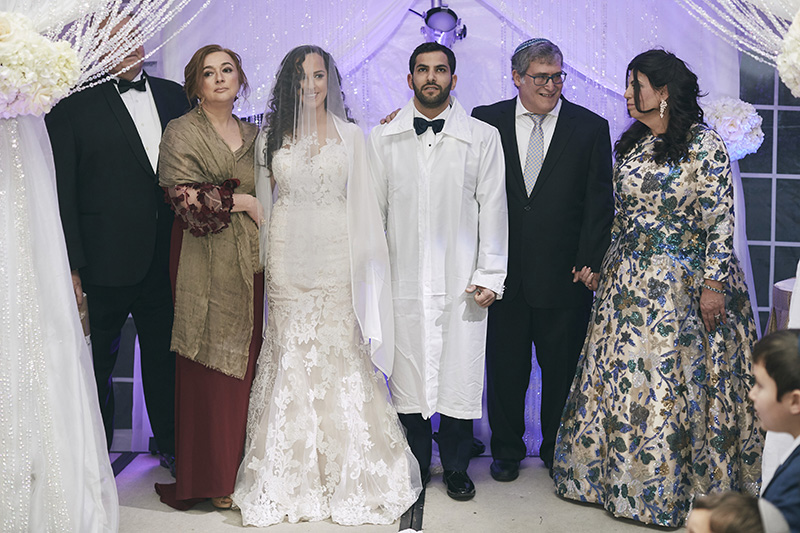 Orthodox Jewish bride and groom with parents