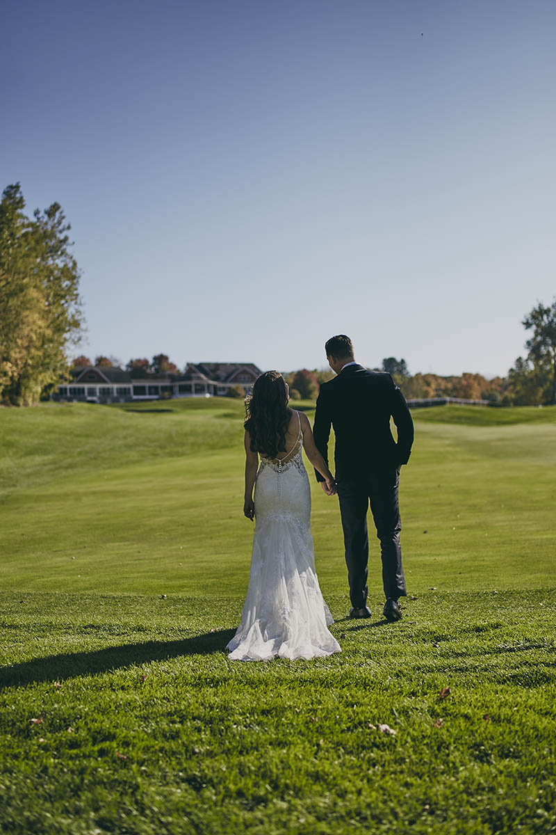 Bride and groom walking away on golf course