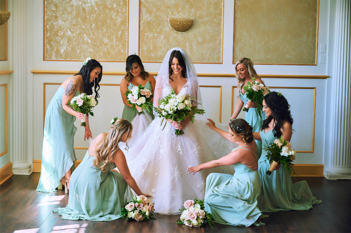 Bride holding flowers while bridesmaids fix the dress