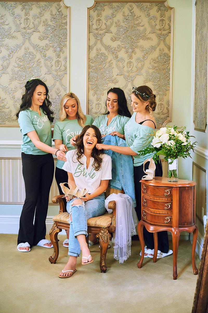 Bride sittin on chair with bridesmaids around her