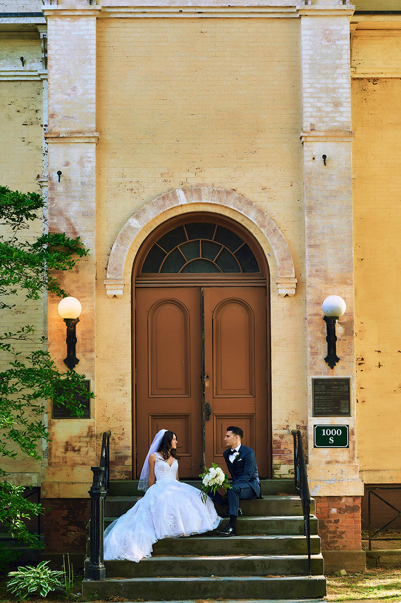 Bride and groom sitting on staircase