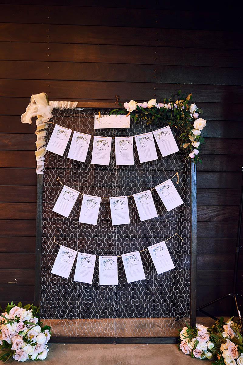 Wedding escort cards hanging on frame