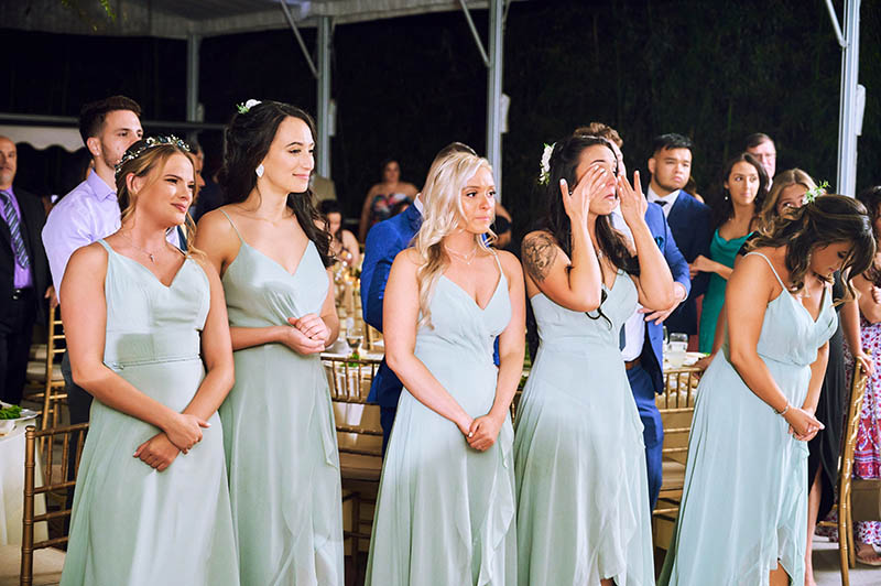Bridesmaids watching first dance and crying