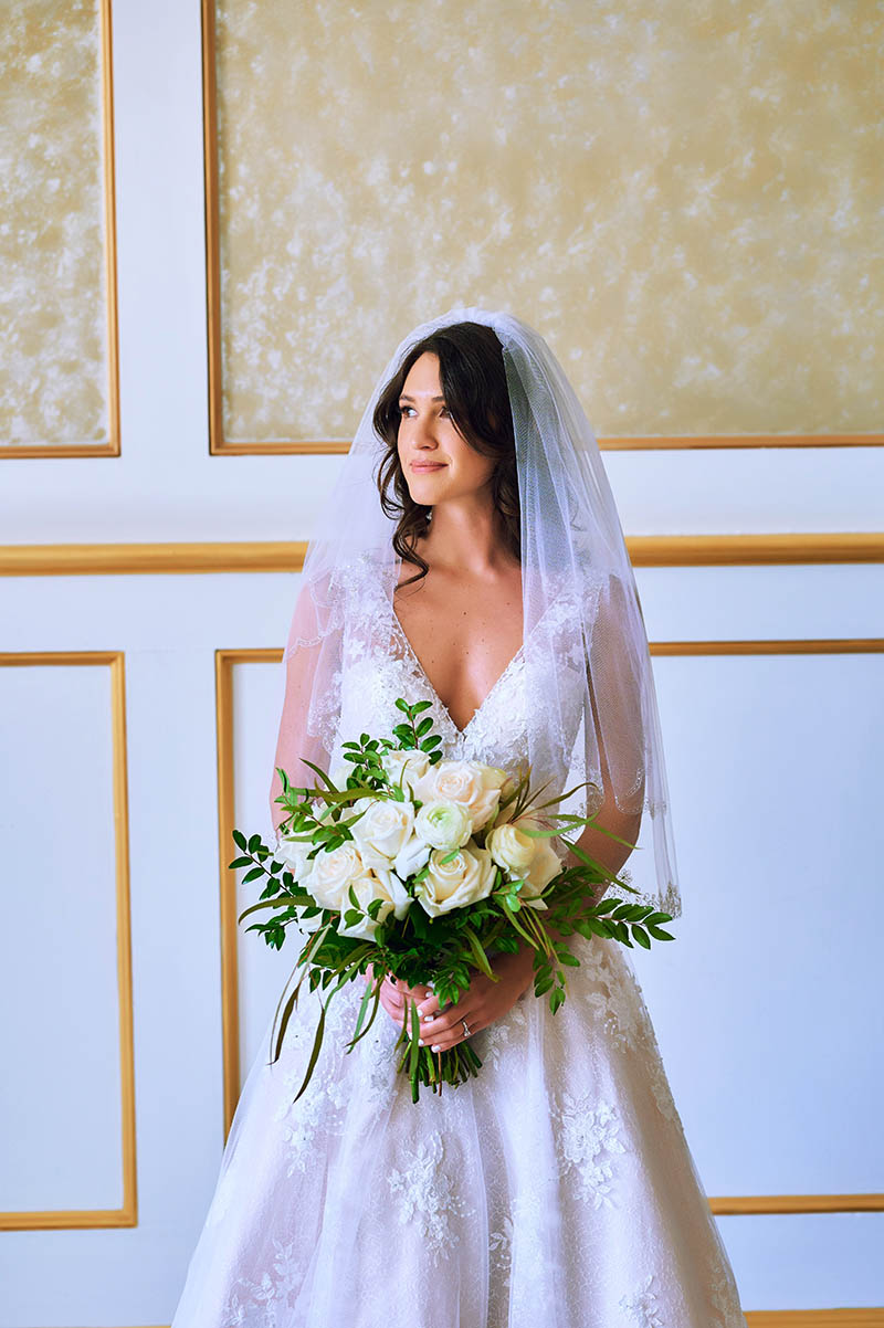 Bride holding flowers and looking out the window